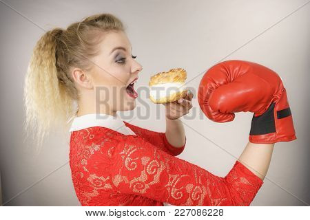 Dieting, Weight Loss Concept. Funny Blonde Woman Holding Yummy Choux Puff Cake With Whipped Cream An