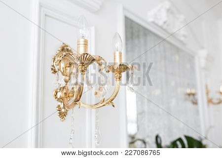 Expensive Interior. Electric Chandelier. White Wall Decorated With Stucco Molding. White Patterned.