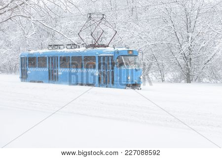 Tram Goes Along The Street During Snowstorm At Winter In Moscow, Russia. Cold And Snowfall In Moscow