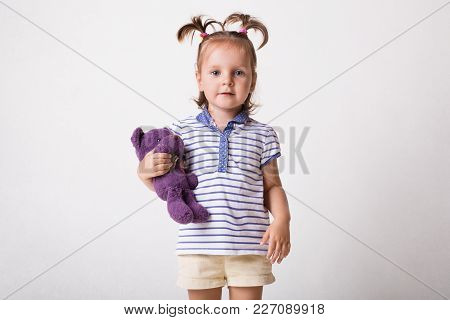 Indoor Shot Of Pretty Little Child In T Shirt And Shorts, Holds Purple Teddy Bear In Hands, Isolated