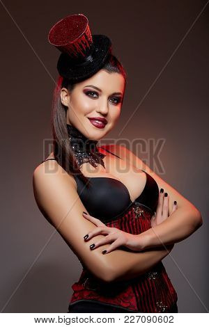Beautiful Young Woman With Long Black Hair And Dark Makeup In Cabaret Style Outfit And Fancy Small H