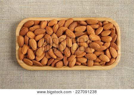 Big Peeled Almonds In Bamboo Plate On Rough Linen Cloth