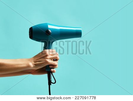 Woman Hands Hold Blue Hair Dryer Pointing At The Corner On Mint Blue Background