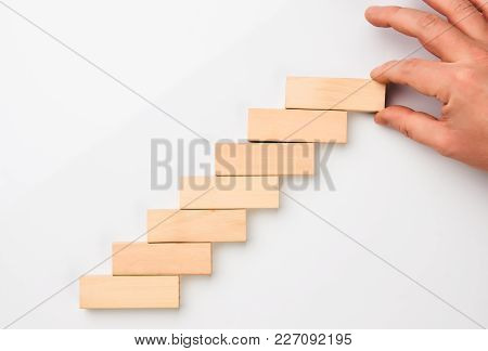 Man Hand Put Wooden Blocks In The Shape Of A Staircase Isolated On White Background With Copy Space.