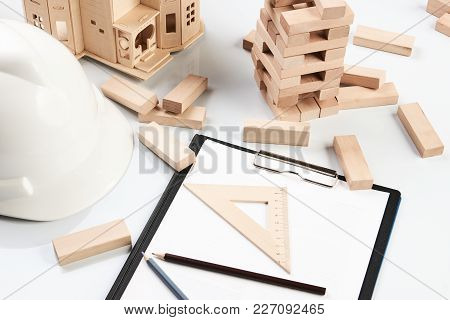 House Model, Wooden Blocks, Helmet And Blueprint Or Architectural Project Isolated On White Backgrou