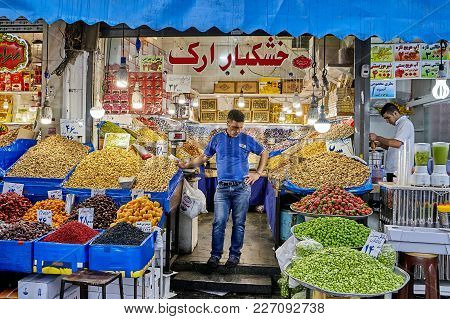 Tehran, Iran - April 29, 2017: Grocer Stands In The Middle Of His Store With Dried And Fresh Fruits.