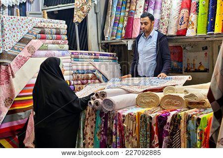 Tehran, Iran - April 29, 2017: Iranian Man Sells Textile To Woman In Hijab In A Fabric Shop.