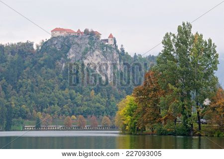 Autumn Foliage Around Bled Lake With Bled Castle On The Precipice In Slovenia