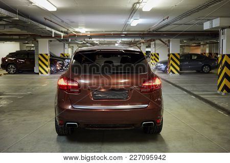 Rear view of new modern car at underground parking.