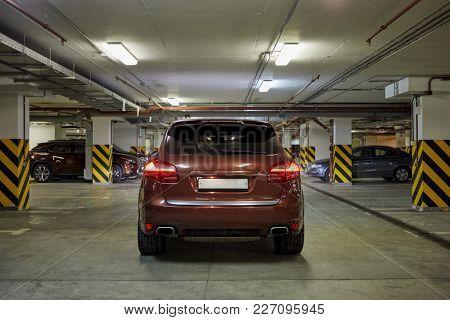 New modern car at underground parking, rear view.