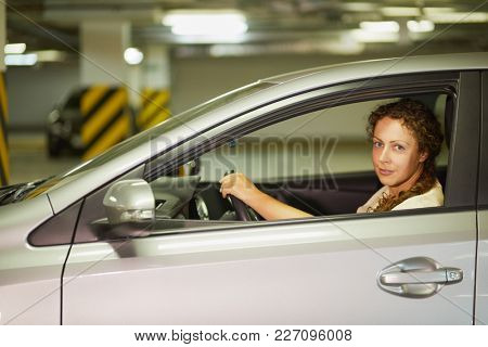 Young woman sits on driver seat in car at underground parking.