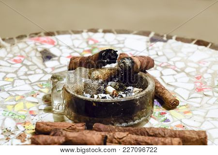 Cigar And Ashtray On The Table Of The Glued Pieces Of Pottery.