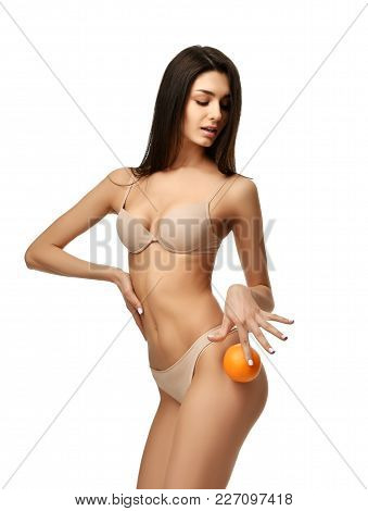 Young Perfect Woman In Underwear Hold Orange Fruit Showing Absence Of Cellulite Isolated On White Ba