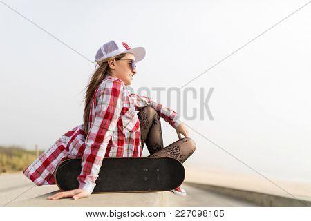 Cute skater girl sitting with skateboard near the beach