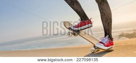 Girl skating a skateboard near the beach