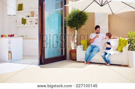 Happy Father And Son Relaxing Under The Shadow Of Umbrella At Rooftop Patio With Open Space Kitchen