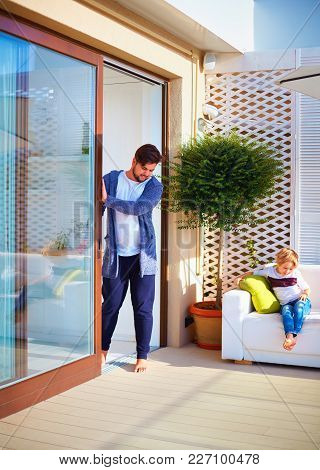 Happy Man Opens Th Sliding Doors On Summer Patio. Family Relaxing At Home