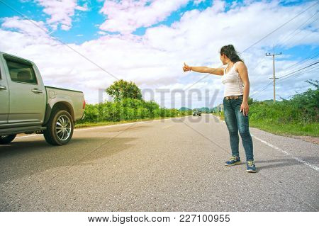Pretty Young Asian Woman With Hand Up Calling Passing Car On Countryside Street.