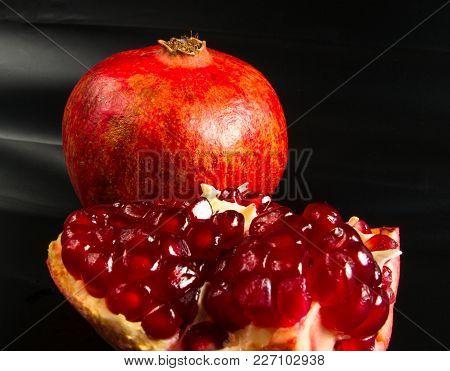 Big Pomegranate Fruit Fnd Seeds On Black Background, Closeup