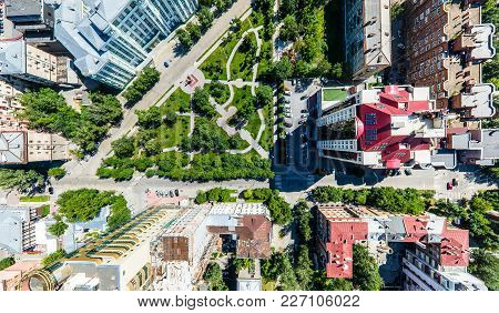 Aerial City View With Crossroads, Roads, Houses, Buildings, Parks And Parking Lots. Copter Drone Hel