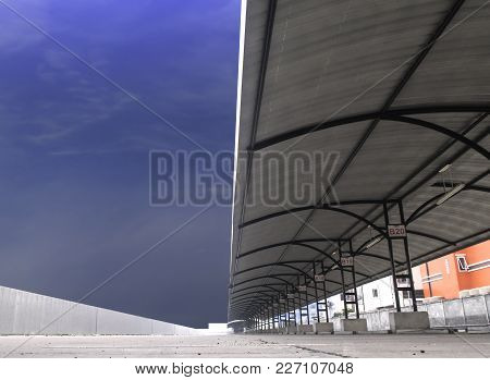 Perspective Of Outdoor Empty Parking Lot With Steel Tube Structure And Metal Sheet Roof Under Blue S