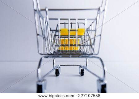 Close Up Of Mini Shopping Cart On White Table,selective Focus