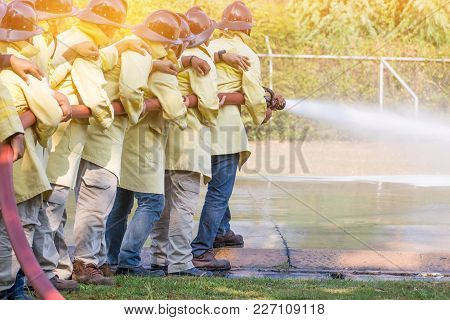 Firemen Using Extinguisher And Water From Hose For Fire Fighting At Firefight Training Of Insurance