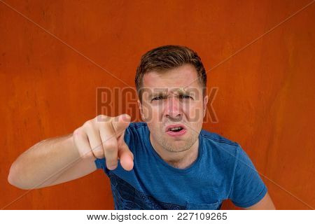 Caucasian Man Dissatisfied Frowns. Poking His Finger Ahead. He Is Unhappy And Angry