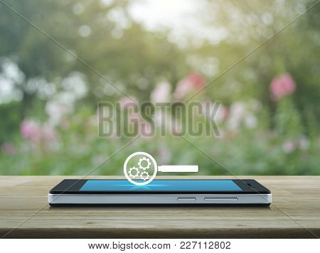 Seo Flat Icon On Modern Smart Phone Screen On Wooden Table Over Blur Pink Flower And Tree, Search En