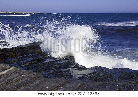 Ocean Waves Crashing And Breaking On The Rocks On The Shore. White Spray Against Blue Ocean Sea And