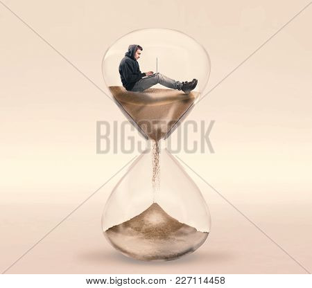 Young Man Working On His Laptop Inside Of A Hourglass. The Concept Of Working With A Deadline.