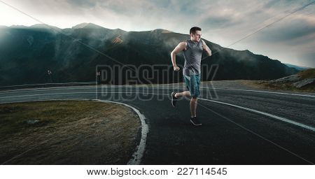 Fitness Man Running On Highway Around The Mountains.