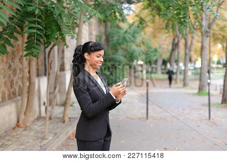 Family Therapist Talking About Wedding With Bride On Smartphone In Park. Beautiful Mix Blood Girl Ha