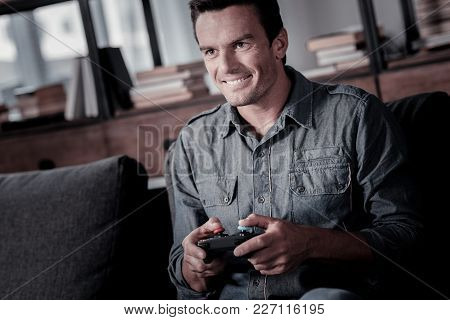 Favorite Leisure Activity. Handsome Adult Guy Wearing Casual Attire Relaxing On A Sofa And Smiling C