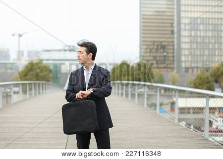 Lawyer In Business Clothes With Smartphone Waiting For Client, Man Standing On Bridge Checking Time