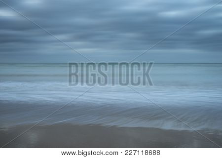 Stunning Long Exposure Landscape Image Of Low Tide Beach With Rocks At Sunrise