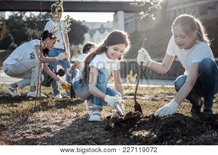 Earth Ecosystem. Cute Pretty Joyful Girl Smiling And Working Together While Planting Trees