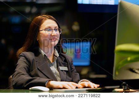 Hotel Manager. A Woman-reception Worker Makes Out An Order For Booking A Room. Profile Shot Of Attra