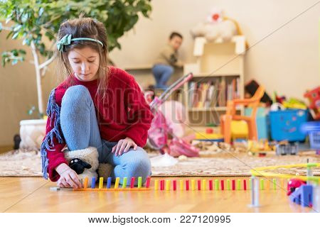 Girl 8 Years Old Is Played In The Room With Toys.