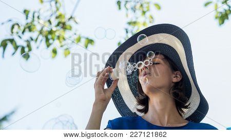Woman Wearing Blue Dress With Hat Blowing Bubbles