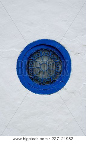 Round Window With A Blue Frame With A Patterned Grille On A White Wall In Tunisia