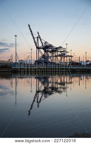 Container Terminal, Shipyard And Cranes At Sunset And Their Reflection.