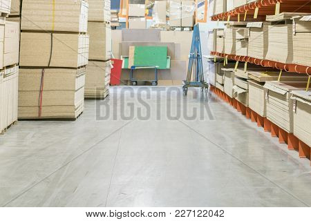 Fiberboard And Chipboard Sheets On Shelves In The Building Materials Store