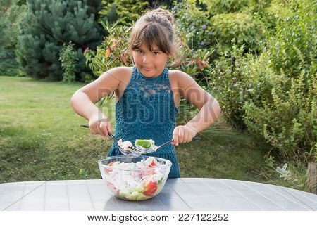 Little Girl Is Diligently Preparing Salad In The Garden. The Girl Is Looking At The Camera.