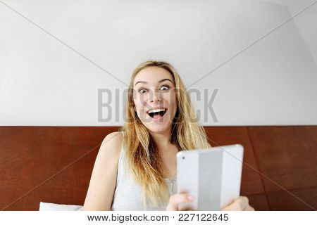 Beautiful Pretty Woman Happy Shocked Face With Tablet Looking At Camera At White Bed. Surprised Girl