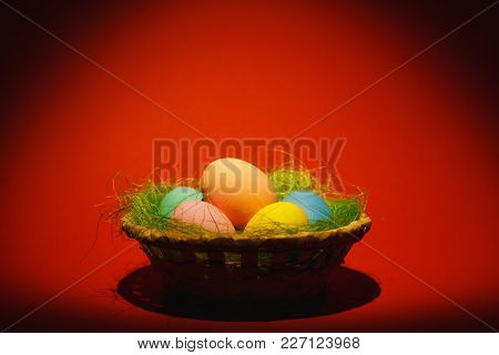 Colorful Pastel Monophonic Traditional Painted Easter Eggs In Basket With Green Grass On Dark Red Ba