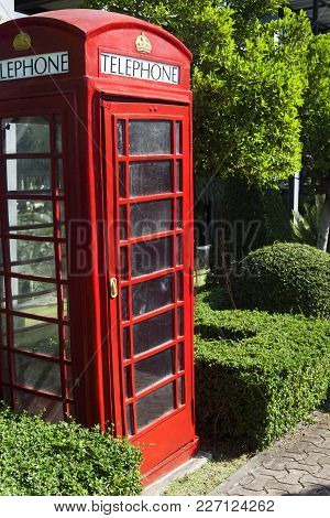 The Red Public Callbox Costs Among Tropical Greens