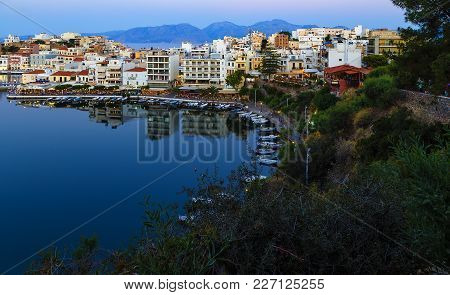 Beautiful Southern Town Of Agios Nikolaos At Summer Evening. Boats Swing On The Water Of The Lake Vo
