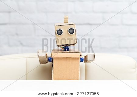 The Robot Sits At The Table. Portrait Of A Robot