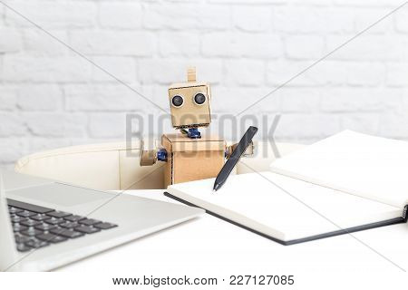 The Robot Holds A Pen In Its Hand And Works Behind The Laptop. Artificial Intelligence